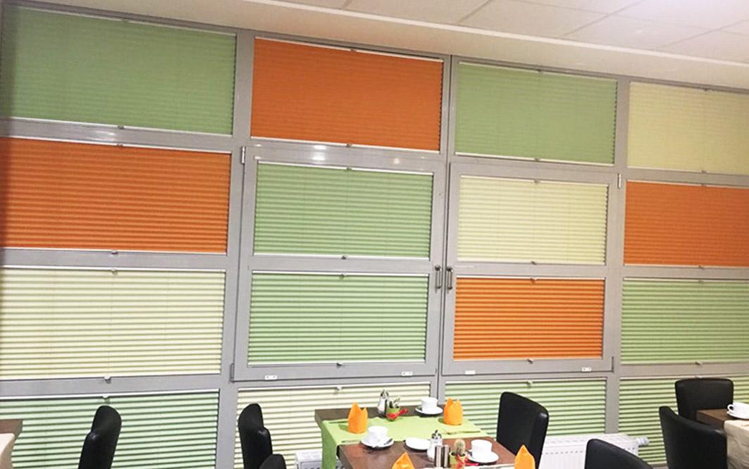 Raum mit Farbenfrohen Fenstern und Tischen und Stühlen