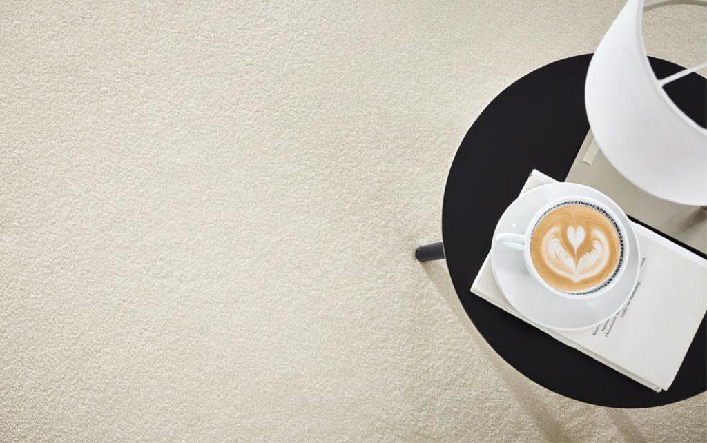 Teppichboden weiss, Flaechenbild mit schwarzen Beistelltisch mit Cappucchino und Lampe