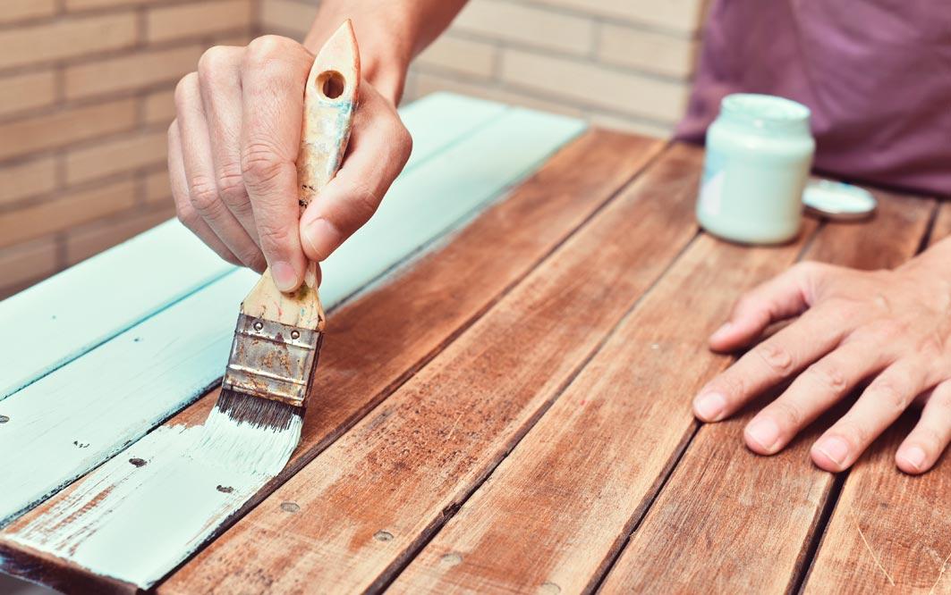 Mann streicht altes Holz mint Farbe aus Glas