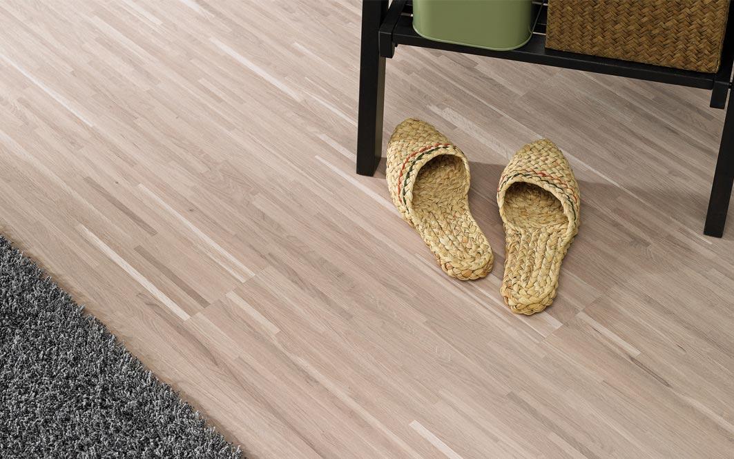 Laminat besch mit grauen Teppich und geflochtene Sandalen, kleines Regal