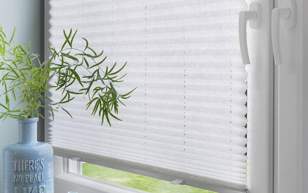 Plisseestoff weiss am Fenster mit blauer Vase mit Pflanze
