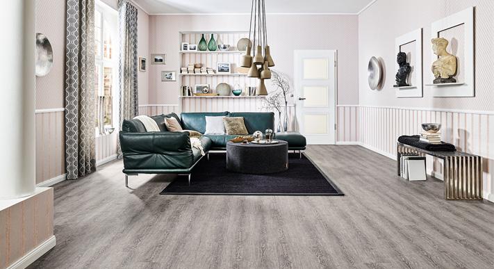 Wohnzimmer mit grauen Boden, großes Sofa mit Kissen und Teppich schwarz