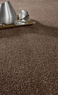 Teppichboden dunkelbraun Struktur mit silbernen Gegenständen