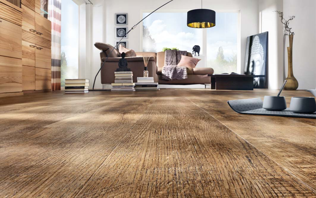 Designboden braun, Wohnzimmer, Froschperspektive mit braunem Sofa und großer Stehlampe schwarz/gold