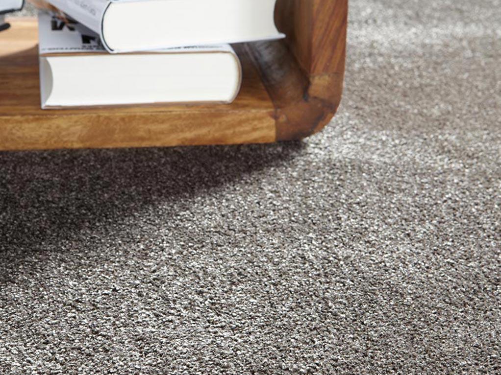 grauer teppich detailansicht, holztisch mit büchern