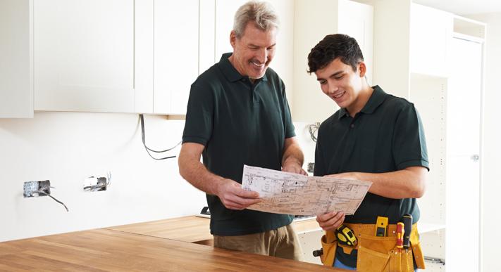 Junger, Aelterer Handwerker bauen Küche ein