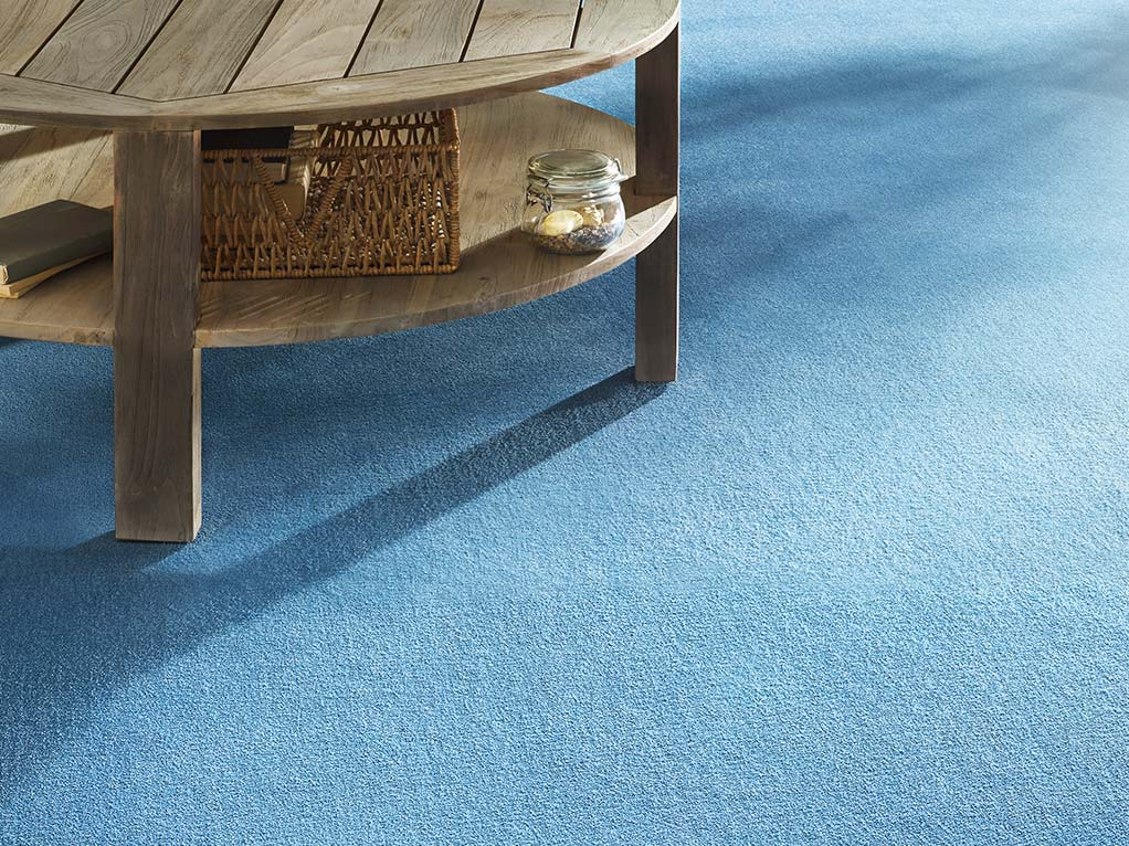 blauer teppichboden mit holztisch