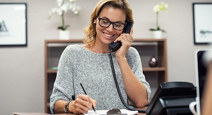 glückliche frau telefoniert am buerotisch und notiert